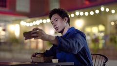 Mixed Race Young Man Takes Selfies With His Food At Outdoor Cafe At Night Stock Footage