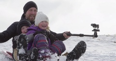 Dad sliding with kids on sled with selfie stick Stock Footage
