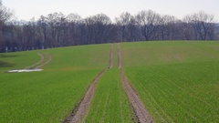 Tire tracks on green rolling hills landscape, agriculture field, forest, Germany Stock Footage