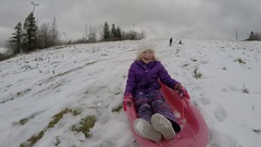 Girl slow motion sledding on snow hill Stock Footage