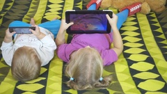 Small children using tablet pc on the bed at home. Brother and siste Stock Footage