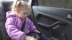 Little girl warm clothing, playing on your tablet PC in car Stock Footage