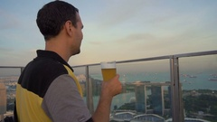 Male tourist drinking beer with view of Singapore, slow motion Stock Footage