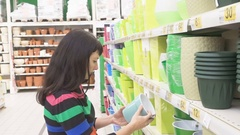 Woman choosing pot for flowers in shop. Woman in a supermarket. Stock Footage