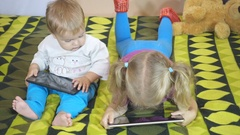 Small children using tablet pc on the bed at home. Brother and sister Stock Footage