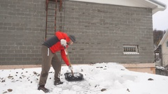 Slow Motion Man with a shovel removing snow from a roof. Stock Footage