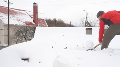 Man with a shovel removing snow from a roof. Stock Footage