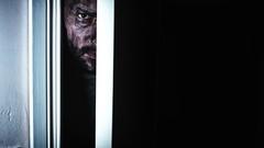 4K Thriller Dirty Man Eye Looking in Door Gap, zoom in slow Stock Footage