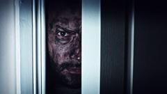 4K Thriller Dirty Man Eye Looking in Door Gap, dolly Stock Footage