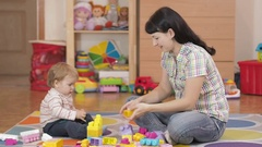 Cute little boy and mother playing with toy blocks at home, Stock Footage