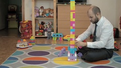 Adult male businessman collects children's building-block Stock Footage