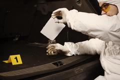 Criminologist collects odor traces on place of crime Stock Photos