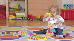 Cute little girl playing with toy blocks at home in room sitting on the floor Stock Footage