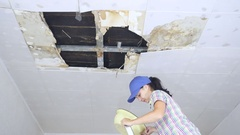 Young Woman Collecting Water In basin From Ceiling. Stock Footage