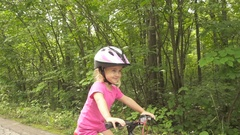 Happy child riding a bike in outdoor. Cute kid in safety helmet biking outdoors. Stock Footage