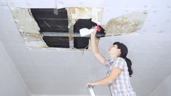 Young Woman cleaning mold on ceiling.Ceiling panels damaged huge Stock Footage