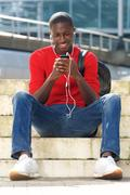 Black male student sitting outdoors and listening  music Stock Photos