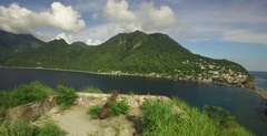 Sailing past cannon to reveal the bay of Soufriere in Dominica by aerial Stock Footage
