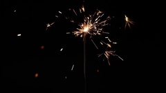 Lightening Christmas sparkler against dark background slow motion footage Stock Footage