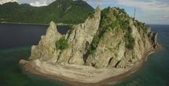 Aerial threads the needle between rock formation to reveal Bay of Soufriere Stock Footage