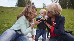 In nature. Happy mom, grandma kissing her baby. The kid on the grass with a toy Stock Footage