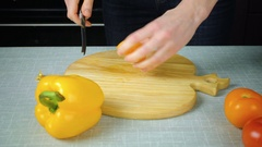 The girl with a knife cuts a yellow tomato Stock Footage