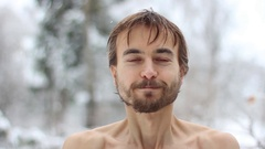 Man washes his face with snow and smiling, face closeup Stock Footage
