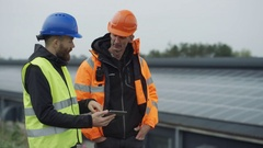 4K Technicians with computer tablet discussing operations at solar energy plant. Stock Footage