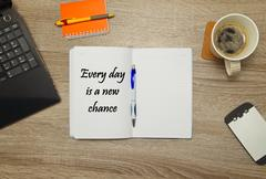 """Open notebook with text """"Every day is a new chance"""" and a cup of coffee on woode Stock Photos"""