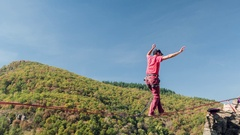 Drone Footage Of Young Man Slacklining Above Mountains During Autumn Tree Season Stock Footage