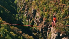 Drone Footage Of Brave Man Slacklining Over Mountains During Autumn Rope Extreme Stock Footage
