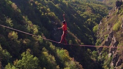 Young Man Balancing On Slack-Line Over Mountains During Autumn Extreme Sport Stock Footage