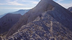 Tracking Shot Of Male Hikers On Top Of Mountain Aerial Landscape Rock Drone Stock Footage