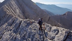 Man With Backpack Hiking On Edge Of Mountain Cliff Extreme Sport Adventure Stock Footage