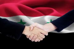 Negotiation handshake with flag of Syria Stock Photos