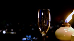 Pouring shampagne in a glass at night party outside, candle beside it Stock Footage