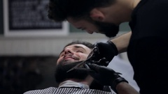 Hairstyling process. Close-up of a barber cutting beard of a young male client. Stock Footage