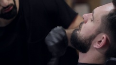 Close-up of a barber using electric razor for cutting beard of a male client. Stock Footage