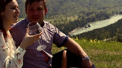 Couple enjoying the outdoors, drinking wine, sitting on a green meadow high in Arkistovideo