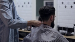 Barber taking off salon cape from client with beard and using a talc Stock Footage