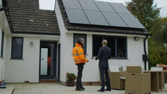 4K Businessman & engineer discuss solar panels on roof at residential property Stock Footage