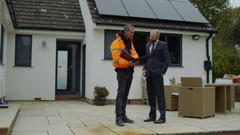 4K Engineer & homeowner discuss solar panels on roof & shake hands on a deal Stock Footage