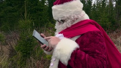 Santa Claus using tablet and laughing Stock Footage