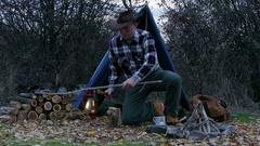 4K.Man   in cowboy hat   cuts firewood for a bonfire. Autumn travel life.  Stock Footage