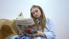 Pretty Blonde Woman Reading A Recipe in Italian Cuisine Cooking Book Stock Footage