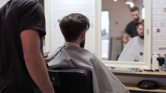 Barber preparing his client for a shaves in a vintage barber shop. Stock Footage