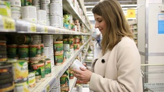 Young woman chooses canned food in the store Stock Footage