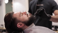 Barber combing beard of client at a barber shop. Stock Footage