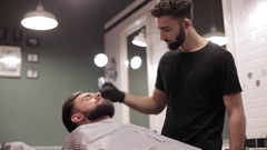 Barber cutting beard and using talc at a barber shop. Stock Footage