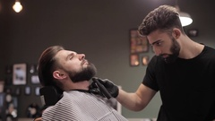Barber cutting beard with electric razor at a barber shop. Stock Footage